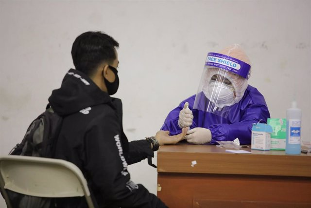 20 May 2020, Indonesia, Bandung: A medical worker wears a protective suit takes a swab from a man during a coronavirus (COVID-19) test at at the Jalak Harupat stadium. Photo: Asep Solihin/Sijori Images via ZUMA Wire/dpa