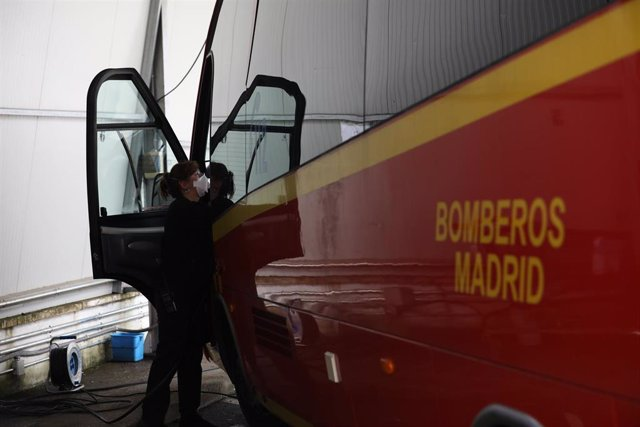 Una mujer desinfecta el interior de un vehículo utilizado por los Bomberos de la Comunidad de Madrid