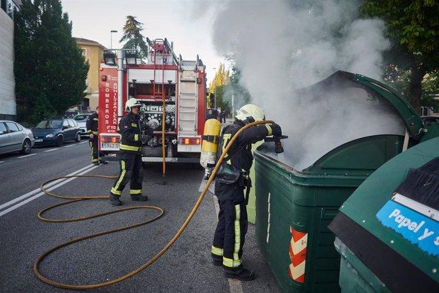 Una dotación de bomberos apaga un contenedor de basura que los manifestantes han prendido en señal de protesta durante la manifestación celebrada en Pamplona en apoyo al preso etarra Patxi Ruiz