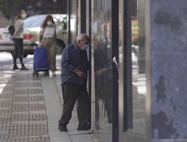 Un hombre por la calle protegido con mascarillas tras el anuncio realizado por el Gobierno, quien ha fijado que la utilización de cualquier tipo de mascarillas sea obligatorio a partir de mañana en la vía pública