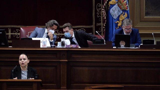 El presidente del Parlamento, Gustavo Matos, durante la intervención de la consejera de Derechos Sociales del Gobierno de Canarias, Noemí Santana, ante el Pleno