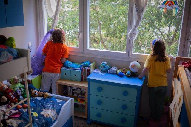 Dues nenes juguen al seu domicili de Barcelona un dia abans que els menors de 14 anys tinguin permeses les sortides de les seves llars, a Barcelona, Catalunya, (Espanya), a 25 d'abril de 2020.