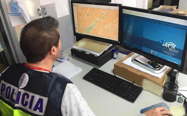 Un policía nacional frente a un ordenador.