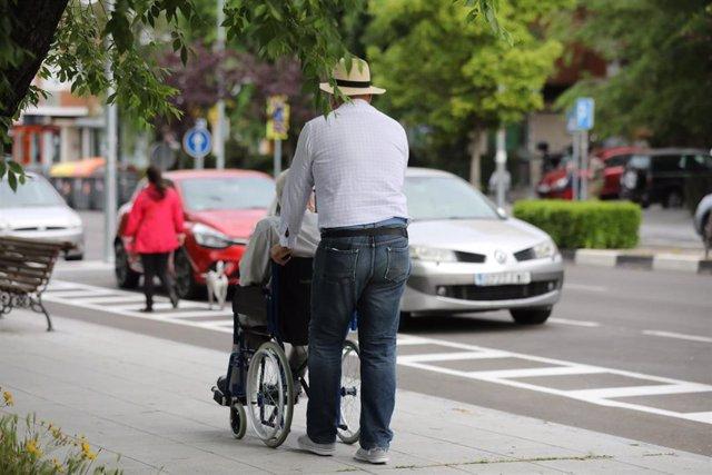 Un hombre pasea a una persona de edad avanzada en silla de ruedas durante su franja horaria permitida en la desescalada por la crisis del Covid-19 donde aquellos mayores de 70 años pueden salir a la vía pública de 10.00 a 12.00 horas y de 19.00 a 20.00 ho