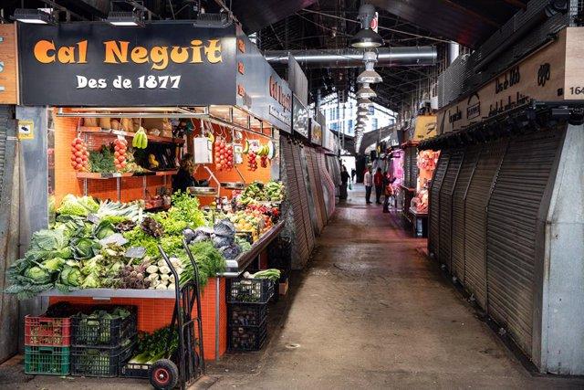 El mercat La Boquería apareix parcialment tancat durant el sisè dia de confinament després de la declaració de l'estat d'alarma per la pandèmia de coronavirus, a Barcelona / Catalunya (Espanya), a 20 de març de 2020.