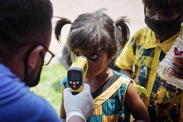 Un hombre toma la temperatura a una niña en la frontera de Joypur, donde llegan los trabajadores migrantes en el Shramik Express. 17 May 2020, India.