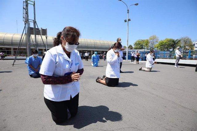 Un grupo de creyentes reza a las puertas de un hospital de Lima en el que están siendo tratados varios pacientes diagnosticados con la enfermedad del nuevo coronavirus.