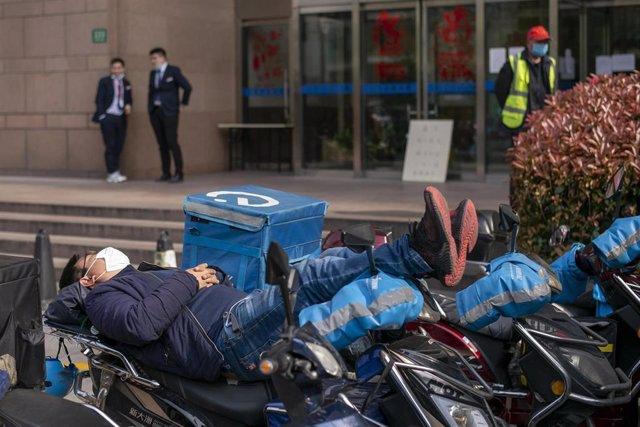 Un repartidor descansa en su motocileta en Shanghai.