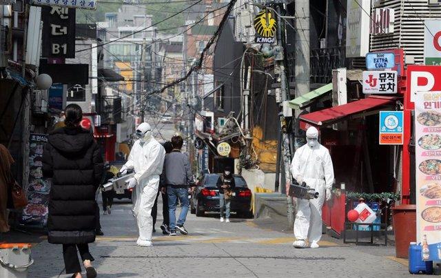 Un grupo e trabajadores desinfectan llas calles del distrito internacional de Itaewon en Seúl, la capital de Corea del Sur.