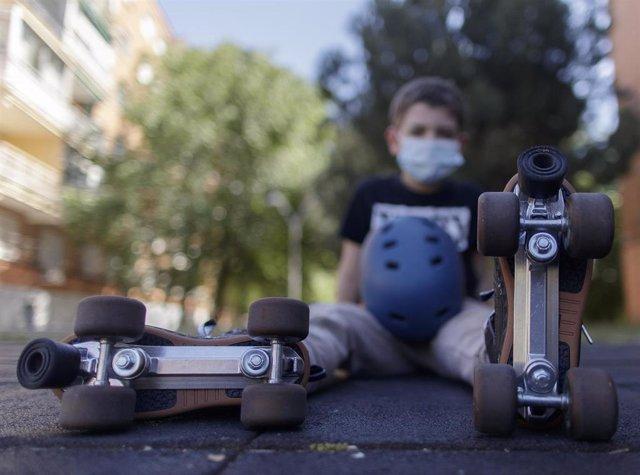 Un niño patina por la calle protegido con una mascarilla tras el anuncio realizado por el Gobierno, quien ha fijado que la utilización de cualquier tipo de mascarillas será obligatorio.