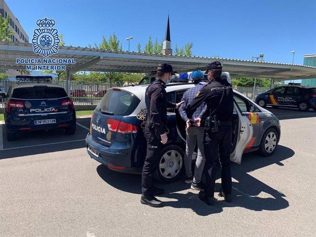 El detenido por robo en un coche es introducido en el vehículo policial