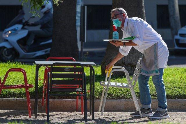 Un camarero limpia las mesas y sillas de una terraza de un bar