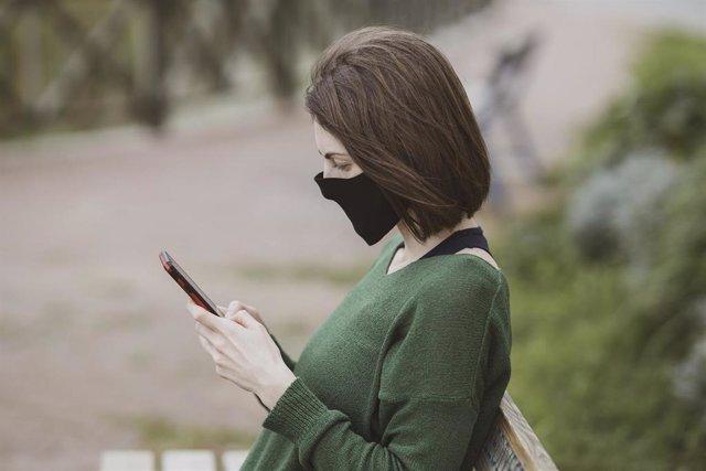 Mujer con mascarilla y smartphone.