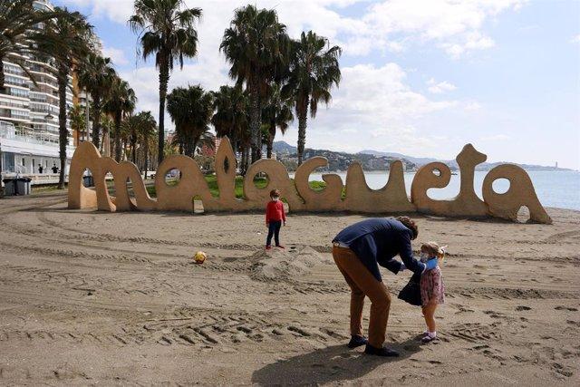Un hombre junto a sus dos hijos protegidos con mascarilla en la playa de La Malagueta el primer día en el que los menores de 14 años pueden salir, en Málaga (Andalucía ,España) a 26 de abril de 2020.
