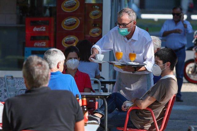 Un camarero sirve a los clientes en una terraza de un bar