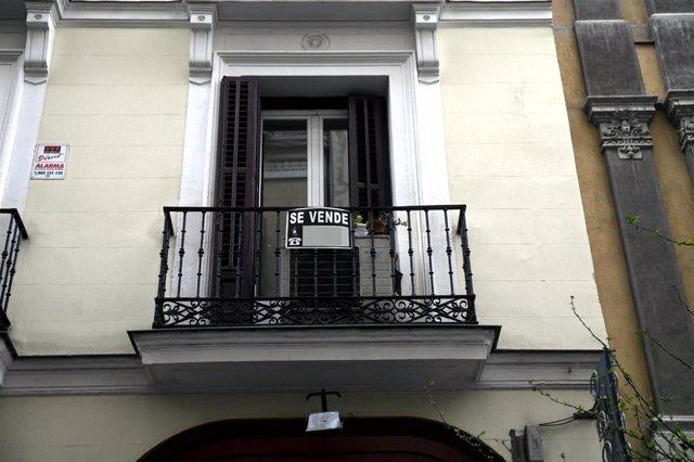 Cartel colgado en un edificio que indica que el inmueble está en venta.