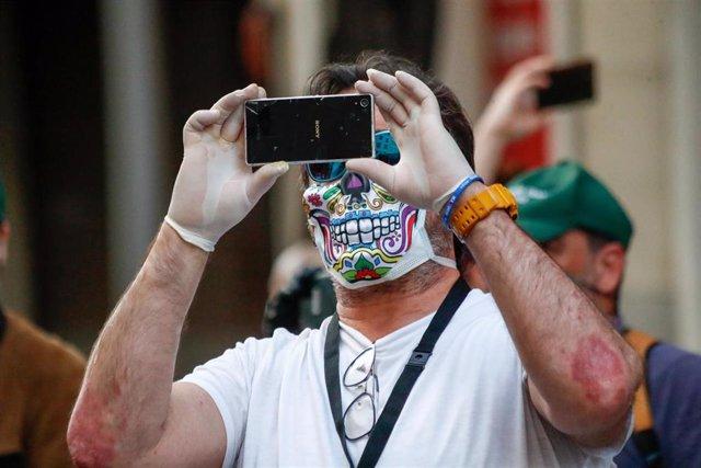 Un hombre con una máscara de calavera toma una fotografía con su móvil durante la manifestación celebrada en la puerta de la sede del PSOE de la calle Ferraz de Madrid, contra la gestión del Gobierno de España contra el coronavirus COVID19 durante la pand