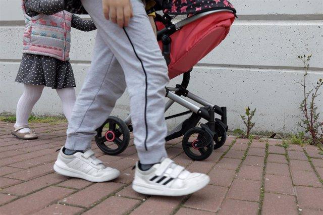 Una niña pasea por la calle empujando un carrito con un bebé de juguete junto a su padre y su hermano