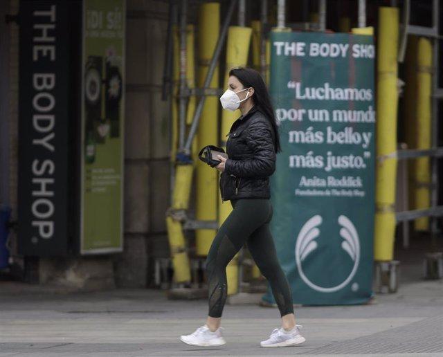 Una mujer camina con una mascarilla por la capital donde desde este pasado lunes las 2.882 farmacias madrileñas han entregado de forma gratuita siete millones de mascarillas FFP2 modelo KN95. En Madrid, (España), a 12 de mayo de 2020.