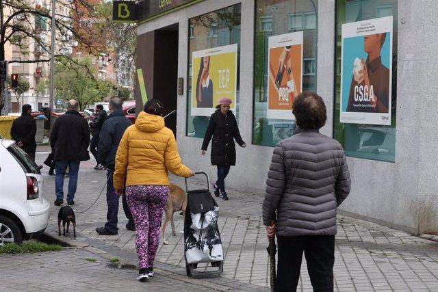 Personas en fila guardan su turno para entrar en una oficina de Bankia dos días antes de que la entidad bancaria inicie el abono de las prestaciones por desempleo del Servicio Público de Empleo Estatal (SEPE), que el banco ha adelantado con el objetivo de