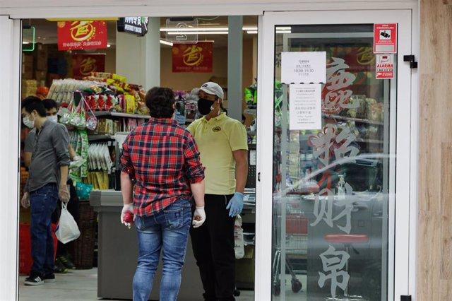 Un trabajador le toma la temperatura a un cliente a la entrada de un supermercado chino