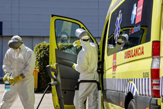 Dos bomberos de la Comunidad de Madrid limpian una ambulancia del SAMUR