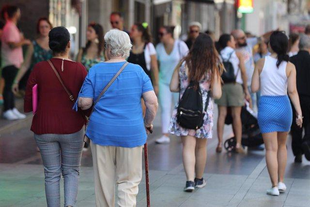 Una dona major passeja del braç d'una altra dona per un carrer de Madrid.