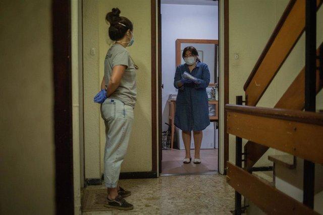 Una voluntaria de la ONG Proactiva Open Arms entrega a una mujer material sanitario en plena crisis del Covid-19. En Barcelona, Cataluña, (España), a 8 de mayo de 2020.