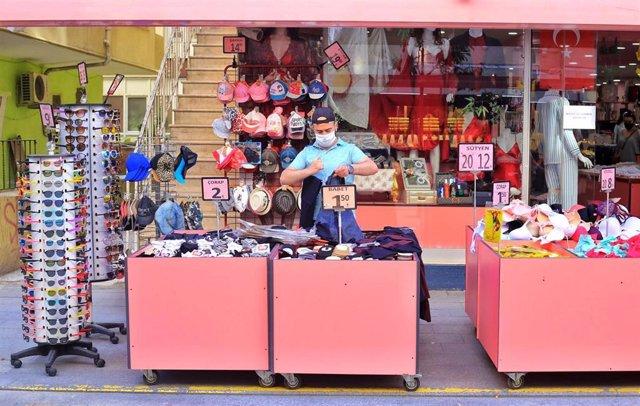 Un dependiente de una tienda de Estambul con mascarilla para evitar contagios.