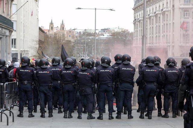 Agentes de la Policía Nacional frente a los manifestantes concentrados en el Congreso de los Diputados en rechazo a la no autorización por el Gobierno a la tramitación parlamentaria de la Iniciativa Legislativa Popular (ILP) presentada por Jusapol