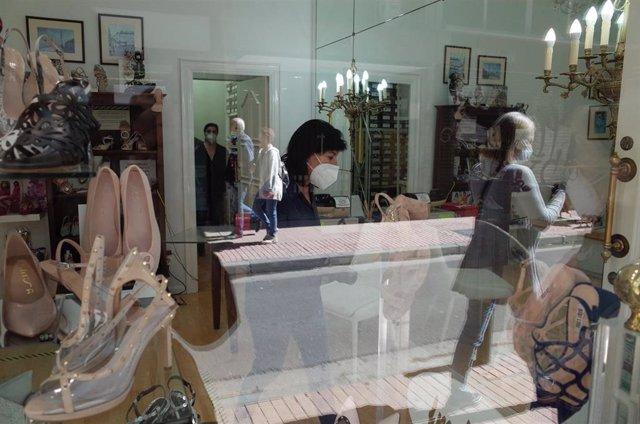 Una zapatería abierta en Zaragoza con clientes y dependientes con mascarilla