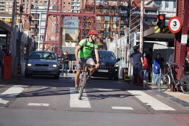 Un ciclista y dos coches cruzan el Puente de Vizcaya, también conocido como Puente Bizkaia que une las dos márgenes de la ría de Bilbao en Bizkaia