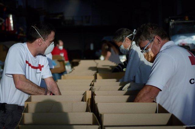 Voluntarios de Cruz Roja preparan lotes de comida