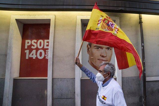 Un hombre alza una bandera de España ante la imagen de Pedro Sánchez en señal de protesta.