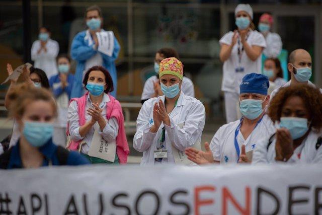 Desenes de membres del personal sanitari protegits amb mascarilla sostenen cartells durant la concentració de sanitaris en el Dia Internacional de la Infermeria a les portes de l'Hospital Vall d'Hebron, a Barcelona, a 12 de maig de 2020.