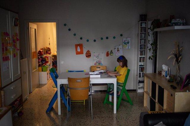 Una niña lee en su domicilio de Barcelona.