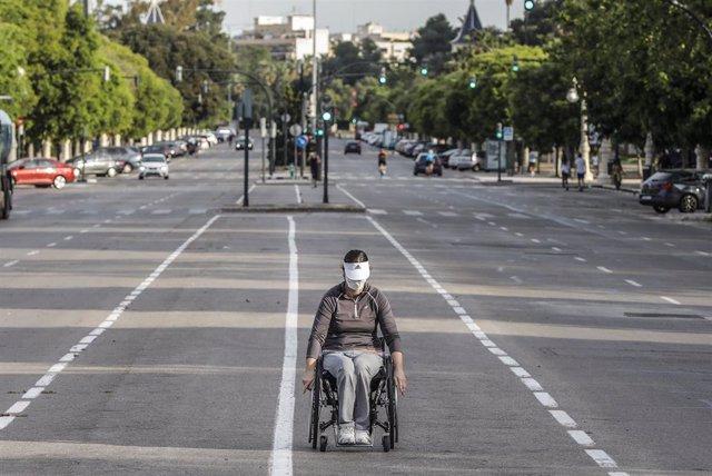 Una mujer en silla de ruedas en el primer día de salida en Valencia tras 48 días en casa por el coronavirus, en  Valencia / Comunidad Valencia (España), a 2 de mayo de 2020.
