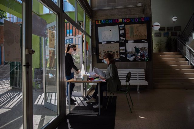Una dona acudeix a l'Institut Escola Coves d'en Cimany, situat al barri El Carmel de Barcelona, durant el primer dia d'atenció presencial per a la preinscripció escolar del curs 2020/2021, a Barcelona, Catalunya, (Espanya), a 19 de maig de 2020.