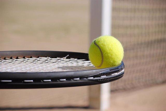 Una raqueta de tenis sostiene una pelota, foto de archivo