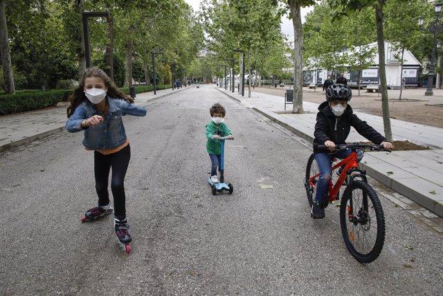Tres nens practiquen esport a l'aire lliure protegits amb mascarillas, el primer dia en el qual els menors de 14 anys poden sortir. A Granada (Andalusia ,Espanya) a 26 d'abril de 2020.