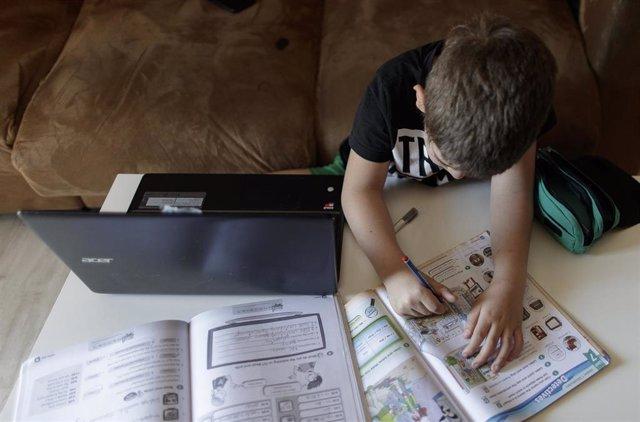 Un alumno de primaria hace los deberes de la asignatura de Inglés con varios libros y un ordenador a menos de un mes de terminar en casa el curso escolar 2019-2020 por la pandemia del Covid-19.