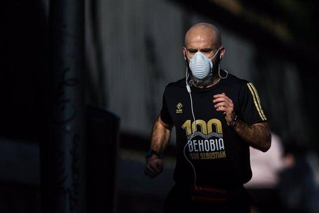 Un hombre protegido con mascarilla sanitaria hace deporte por la calle Alcalá de la capital