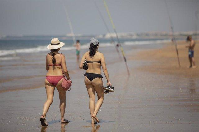 Dos personas pasean por la playa de Punta Umbría, durante la fase 1