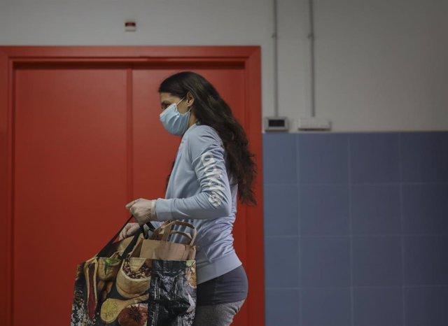 Una mujer con bolsas de menú tras ser atendida por una trabajadora de la Fundación Don Bosco, y recibir alimentos del Proyecto Fraternitas. En Sevilla, (Andalucía, España), a 16 de abril de 2020.