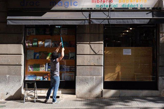 Una persona sube el cierre de una librería en Palma en la fase 1.