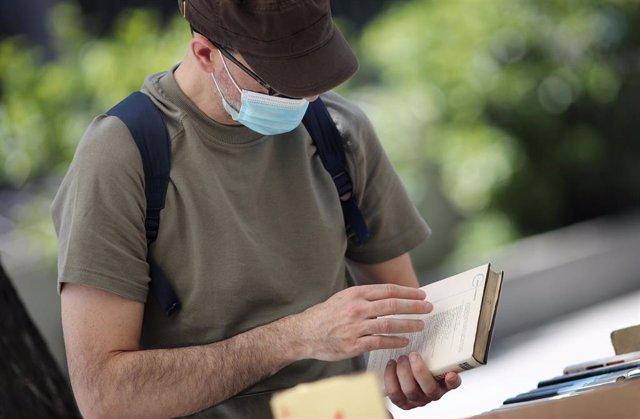 Un hombre protegido con mascarilla observa un libro