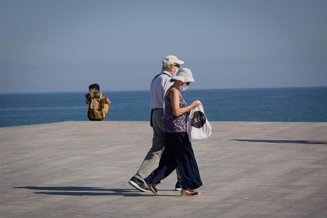 Dos personas protegidas con mascarillas pasean por el Paseo Marítimo de la Playa de la Barceloneta durante el día 66 del estado de alarma decretado por el Gobierno a causa del Covid-19, en Barcelona/Catalunya (España) a 20 de mayo de 2020.