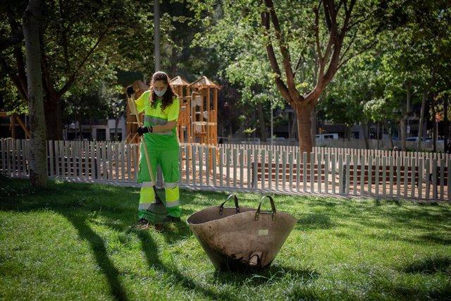 Una operaria de limpieza del servicio municipal rastrilla el césped de un parque
