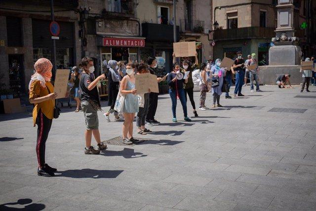 Decenas de personas de la Red vecinal de Apoyo Mutuo Ciutat Vella, ataviadas con mascarillas y con carteles, se concentran en la Plaza Aureli Campmany bajo el lema 'Paremos la epidemia de la crisis social' para pedir que se garantice el acceso a recursos