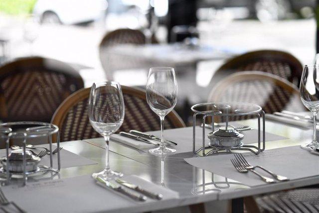 Una mesa en una terraza con unos hornillos, copas de vino y cubiertos.